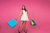 Beautiful young woman in white dress with shopping on pink background. Concept of shopping, summer sale
