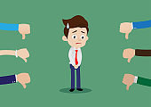 Unsuccessful and sad businessman with many thumbs down hands around him