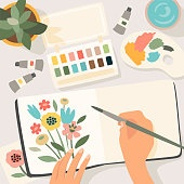 Stay at home. Woman paints flowers in sketchbook. Vector illustration.