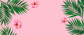 Creative flat lay top view of green tropical palm leaves with flowers  on pink paper background.