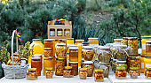 Assortment of honey jars at market stall. Sale of natural honey in fair outdoor.