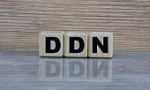 concept word DDN on cubes with a mirror image on a wooden background