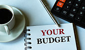 YOUR BUDGET - words written in a notebook against the background of a calculator and a cup of coffee