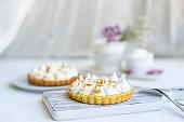 Mini tartlet with fruit jam and meringue. Tart with Italian meringue cream on white plate on table.