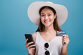 Asian smiling beautiful women wear a wide hat and sunglasses using smartphone shopping online with credit card isolated in blue color background.Concept of Travel business with Promotion and Sale.