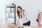 Beautiful asian woman fashion designer standing in the clothing store and studio. In front of the laptop and using smartphone.Business online influencer on social media concept.