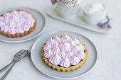 Mini tartlet with fruit jam and pink meringue. Tart with Italian meringue cream on white plate on table.