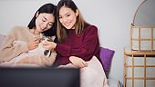 Young beautiful Asian women lesbian couple lover watching television on bed with cat together in bed room at home with smiling face.Concept of LGBT sexuality with happy lifestyle together.