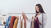 Beautiful asian woman fashion designer standing in the clothing store and studio.Small Business online influencer concept.