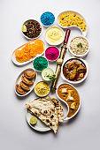 Happy Holy concept  showing Indian assorted lunch food like paneer butter masala, naan, jeera rice, black chana fry, jalebi, fujiyama, thandai and Farsan with holi colours and pichkari