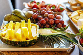 Plate of fresh sliced fruits - juicy pineapple, grapes, pears. Snacks on the table.