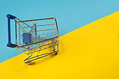 Empty push cart seen from an high angle on a blue and yellow background as a concept for shopping