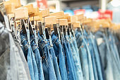 Colorful jeans hanging on a hanger in a store