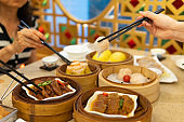 People eating Guangdong dum sum with chopsticks in the restaurant
