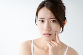 Young asian woman worrying about her skin.
