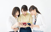 Group of asian girls showing smart phones each other.