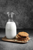 Chocolate and sunflower seed cookies with milk in glass bottle, Cookies and milk on rustic background