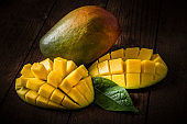 Closeup of one ripe whole and one sliced mango isolated on a wooden table