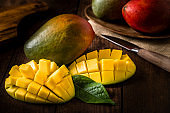 Whole and sliced mangoes with a kitchen knife on a rustic wooden table
