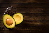 Whole and sliced avocado with copy space on a rustic wooden table