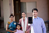 Rural family with real estate agent showing digital tablet