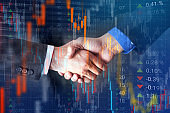 Businessmen handshake against digital stock market data background