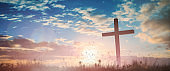 Silhouette jesus christ crucifix on cross on calvary sunset background concept for good friday he is risen in easter day, good friday worship in God, Christian praying in holy spirit religious.