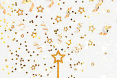 Glittering magic wand in a star shape with golden confetti.