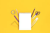 Notepad mockup with stationery on a bright yellow background.