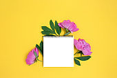 Empty notebook mockup with bouquet of peony flowers