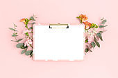 Clipboard mockup with frame made of flowers and eucalyptus. Festive floral composition with copy space on a pink pastel background.