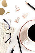 White desk with mug of coffee, paper clips, glasses, notepads, calligraphic pen and pencils on white desk