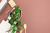 Frame made of green leaves, canvas bag, metal bottle and cutlery. Plastic free concept with place for text on brown background.