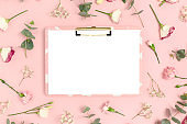 Clipboard mockup with blank paper card. Pattern made of flowers on a pink pastel background.