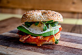 Breakfast Bagel with Egg, Greens, Avocado, Bacon, Sausage and Cheese on a Rustic Cutting Board