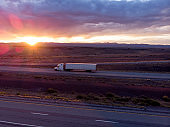 Long Haul Freight Hauler Semi-Truck and Trailer Traveling on a Four-Lane Highway in a desolate desert at dusk or dawn
