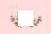 Blank paper card mockup with carnation flowers, eucalyptus and stars confetti. Holiday concept with place for text on a pink pastel background.