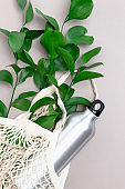 Reusable shopping bag with green leaves and metal bottle. Plastic free concept.
