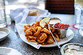 A Delicious Plate Of Deep Fried Calamari, Squid Fried To Perfection Cajun Style, Served With A Side Of Freshly Made Garlic Aioli Sauce And Cocktail Sauce, Fresh Lemon Wedges On The Side