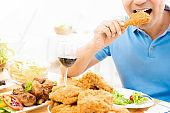 Young man eating fried chicken