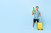 Smiling handsome Asian tourist man traveling with water gun and baggage during Songkran festival studio shot blue background with copy space