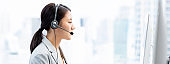Young Asian businesswoman wearing headsets working as a customer service operator in call center city office  banner background