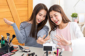 Two pretty Asian beauty influencers waving to the camera while recording video