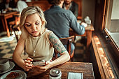 Blonde woman sitting alone in local bar, surfing the net and waiting for a friend