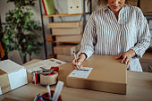 Businesswoman writing on bar code label on delivery package