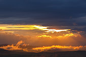 Low clouds in backlight over a landscape at sunset