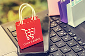 Business concept : red small paper shopping bags with smartphone on notebook keyboard. Online shopping or order goods on the internet It is more popular. can buy everything from home or office.