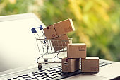 Paper boxes in a shopping cart on notebook keyboard. Ideas about e-commerce or electronic commerce is a transaction of buying or selling goods or services online over the internet.
