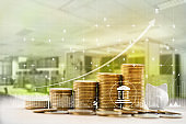 Financial and banking / Finance and business concept:  Arrange rows of increasing coins and graph growth business investment on workplace background. depicts investing money for earning growth.