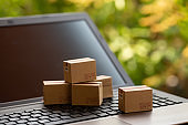 Online shopping, ecommerce and delivery service concept: Paper cartons or boxes on notebook keyboard